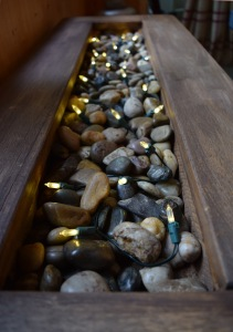 In the centre of the table, I put river rocks and fairy lights. The lights add soft light at night.