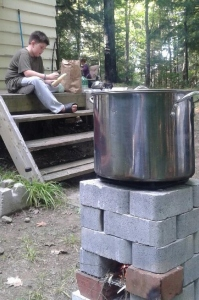The rocket stove being used to heat water to boil corn.