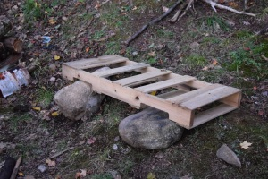 The pallet rests on the ground at the back and on the rocks in the front.